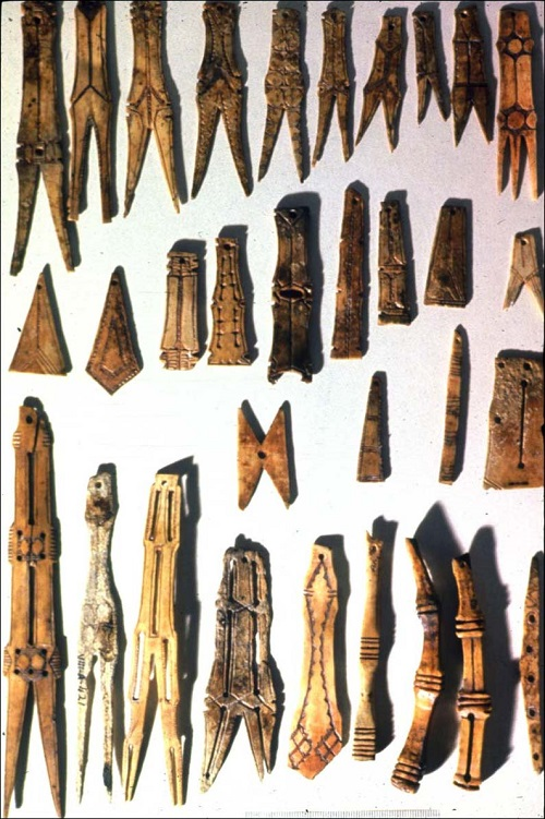 Beothuk bone carvings with incised patterns on both faces, rubbed with red ochre.