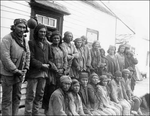 An early 20th century photograph of Innu traders gathered outside the Hudson's Bay Company post in Davis Inlet, Labrador.