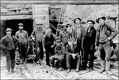 Bell Island miners at opening of No. 3 Slope, about to descend for the 6:00 p.m. shift. Candles on hats are to light their wayunderground.