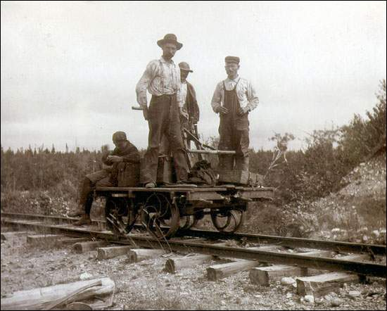 Foreman Billy Best and sectionmen on a pump car, probably near Port Blandford.