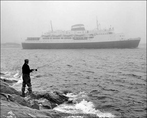 Ferry MV William Carson with fisherman in foreground at Channel–Port aux Basques, NL, May 1959.