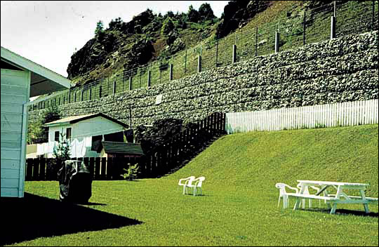 Retaining wall constructed in Taylor's sub-division, Springdale at a cost of $286,000. The sub-division was built at the base of a highly fractured basalt cliff.