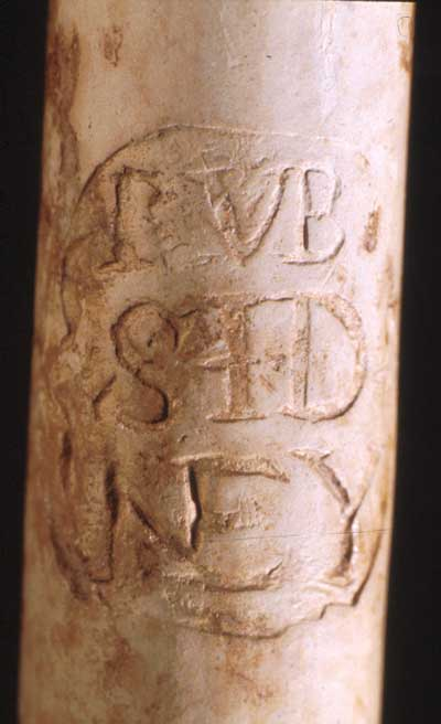RVB/SID/NEY Incuse. Stamped or mould imparted on the stem. Initials RS sometimes moulded on sides of heel. Stem bore size: 5/64ths. Mark identified as Reuben Sydney, Southhampton pipemaker 1687-1748. Refer to Oswald 1975:173; Walker 1971:81.
