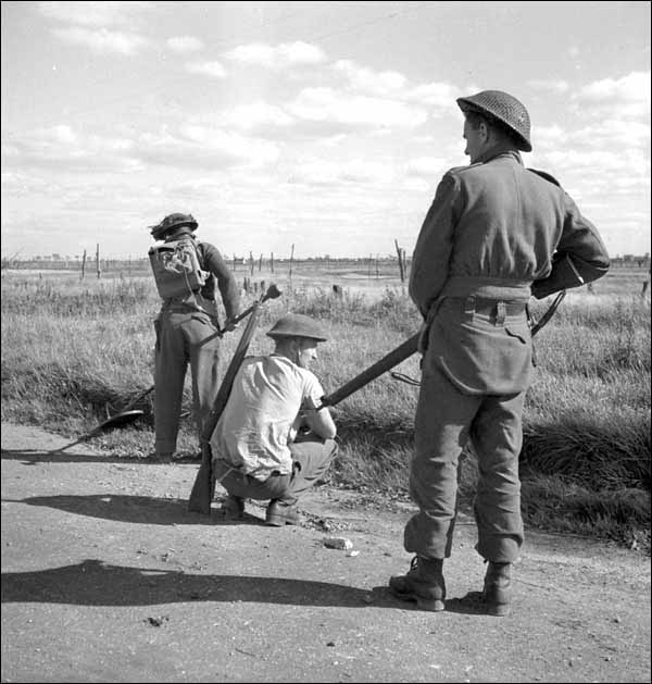Servicemen with the 7th Field Company, Royal Canadian Engineers check for mines on a road in Bergues, France.