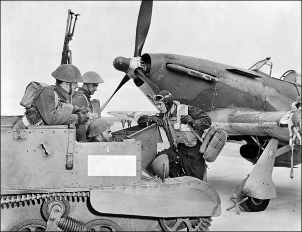 Three infantrymen talk with a flight officer. In the background is a Hawker Hurricane XII aircraft.