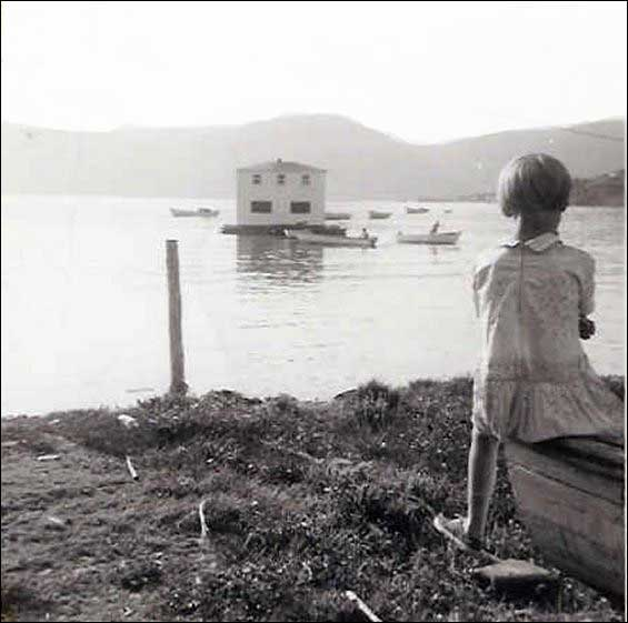 As a young girl looks on, the house of Mike and Hilda Symmonds is floated from North East Crouse to Conche, Great Northern Peninsula, NL. To view other images visit the Maritime History Archive's  Moving House section of their Resettlement site.
