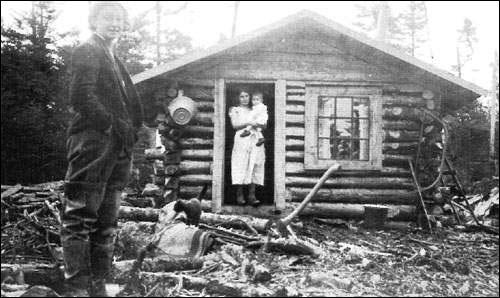 School teacher Claire Cochius, standing in front of one of the first Markland homesteads.